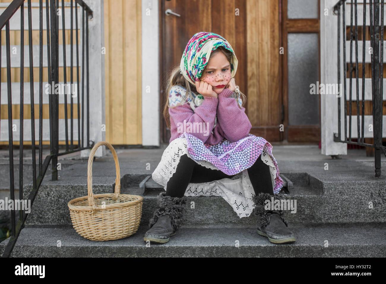 Schweden, nachdenkliches Mädchen (4-5) als Ostern Hexe mit Ostern Korb sitzen auf Schritte gekleidet Stockbild