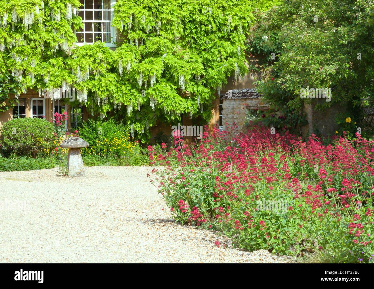 Vordere Bauerngarten mit roten Blumen entlang steinerne Auffahrt ...