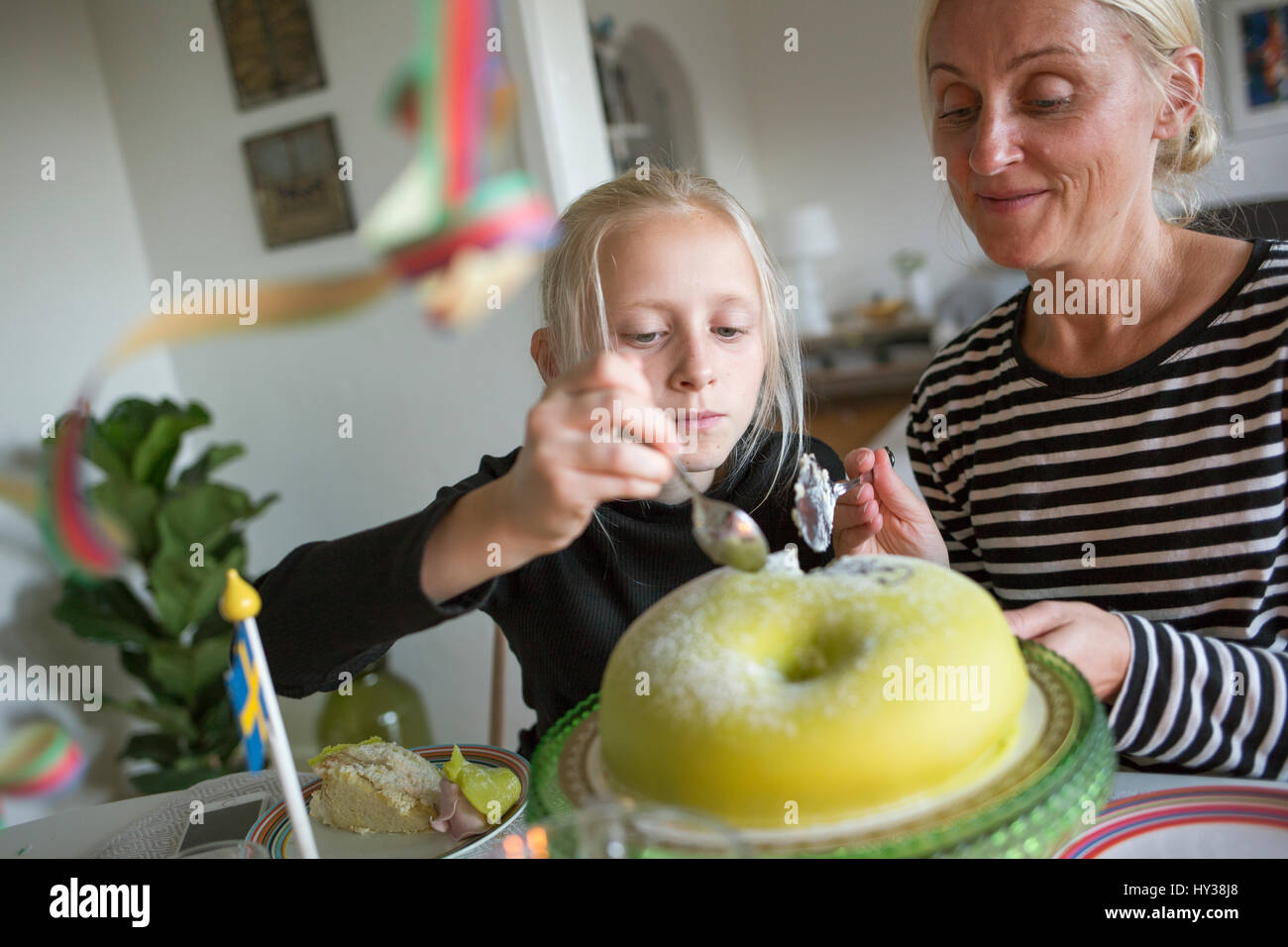 Schweden, Mädchen (12-13) und reife Frau schneiden Geburtstagstorte Stockbild