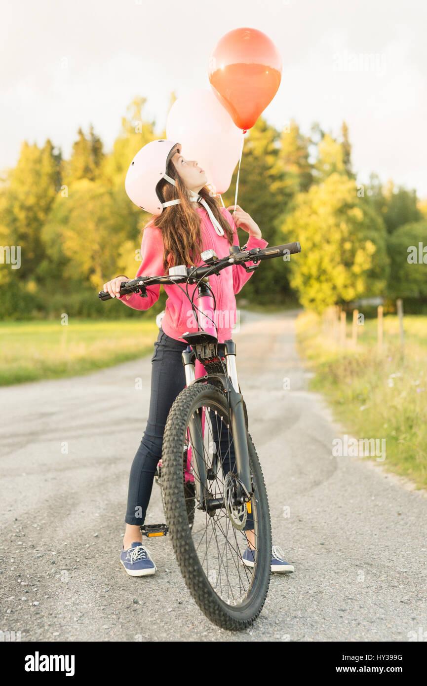 Schweden, vastmanland, hallefors, Bergslagen, Mädchen (10-11) Reiten Fahrrad bei Sonnenuntergang Stockbild