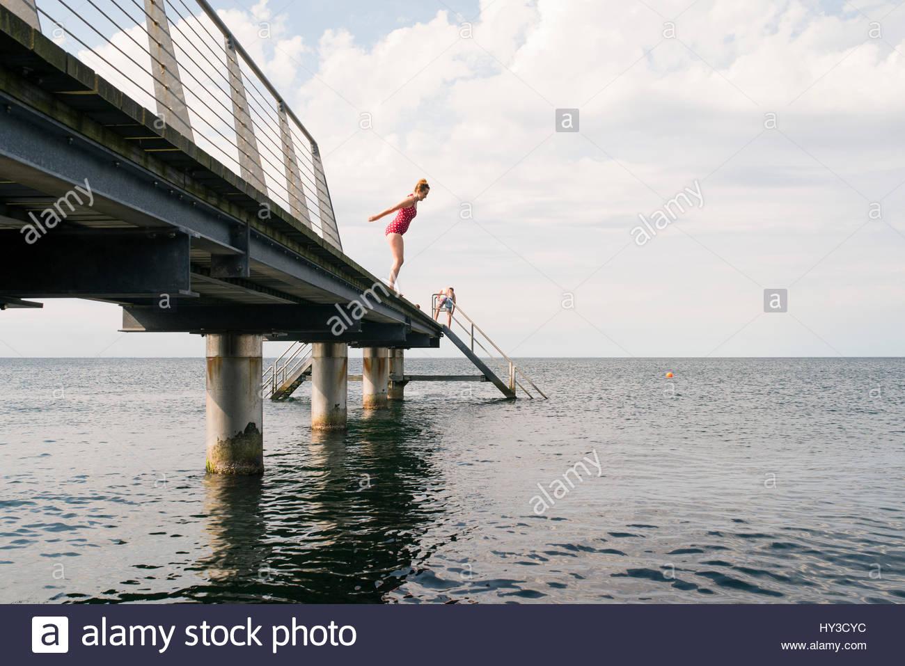Schweden, Skåne, Malmö, Frau ins Wasser springen vom Pier Stockbild