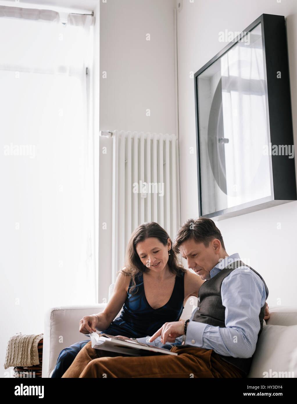 Deutschland, Paar sitzt auf dem Sofa ein Buch lesen Stockbild