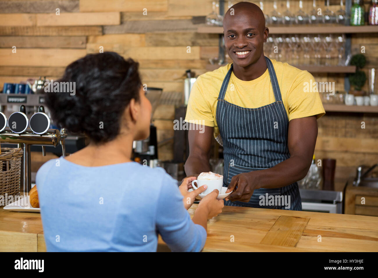 Porträt von glücklich männliche Barista Kaffee an Kunden im Coffee Shop serviert Stockfoto