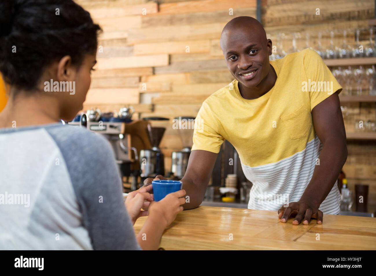 Porträt von männlichen Barista Kaffee an weibliche Kunden im Café serviert Stockfoto