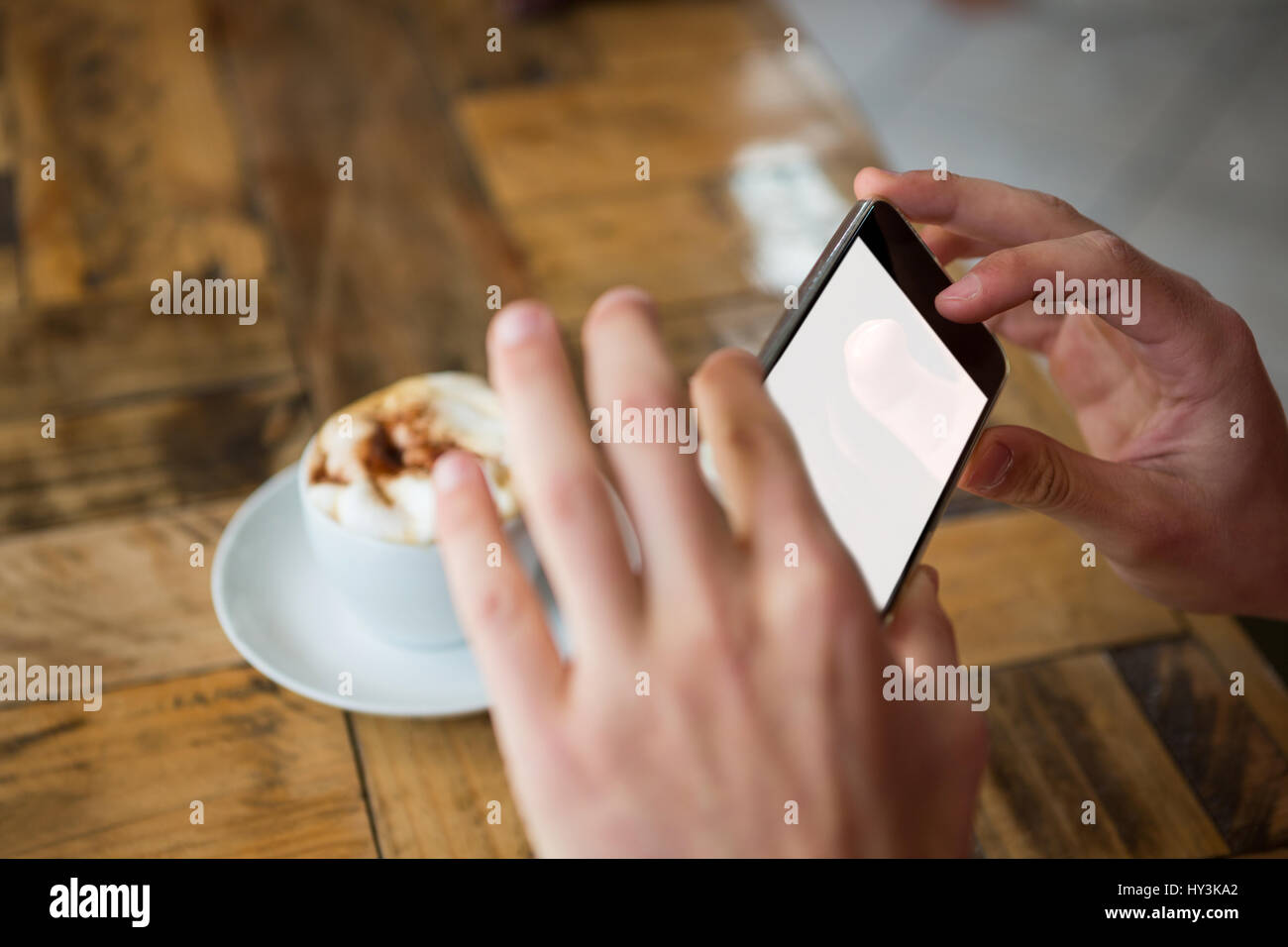 Nahaufnahme der Mannhände fotografieren Kaffee durch Smartphone im café Stockfoto