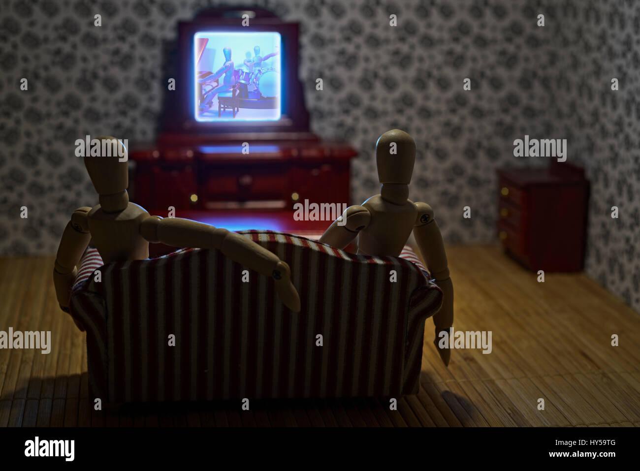 Das Leben der Holzfiguren - Paar schaut TV Stockbild