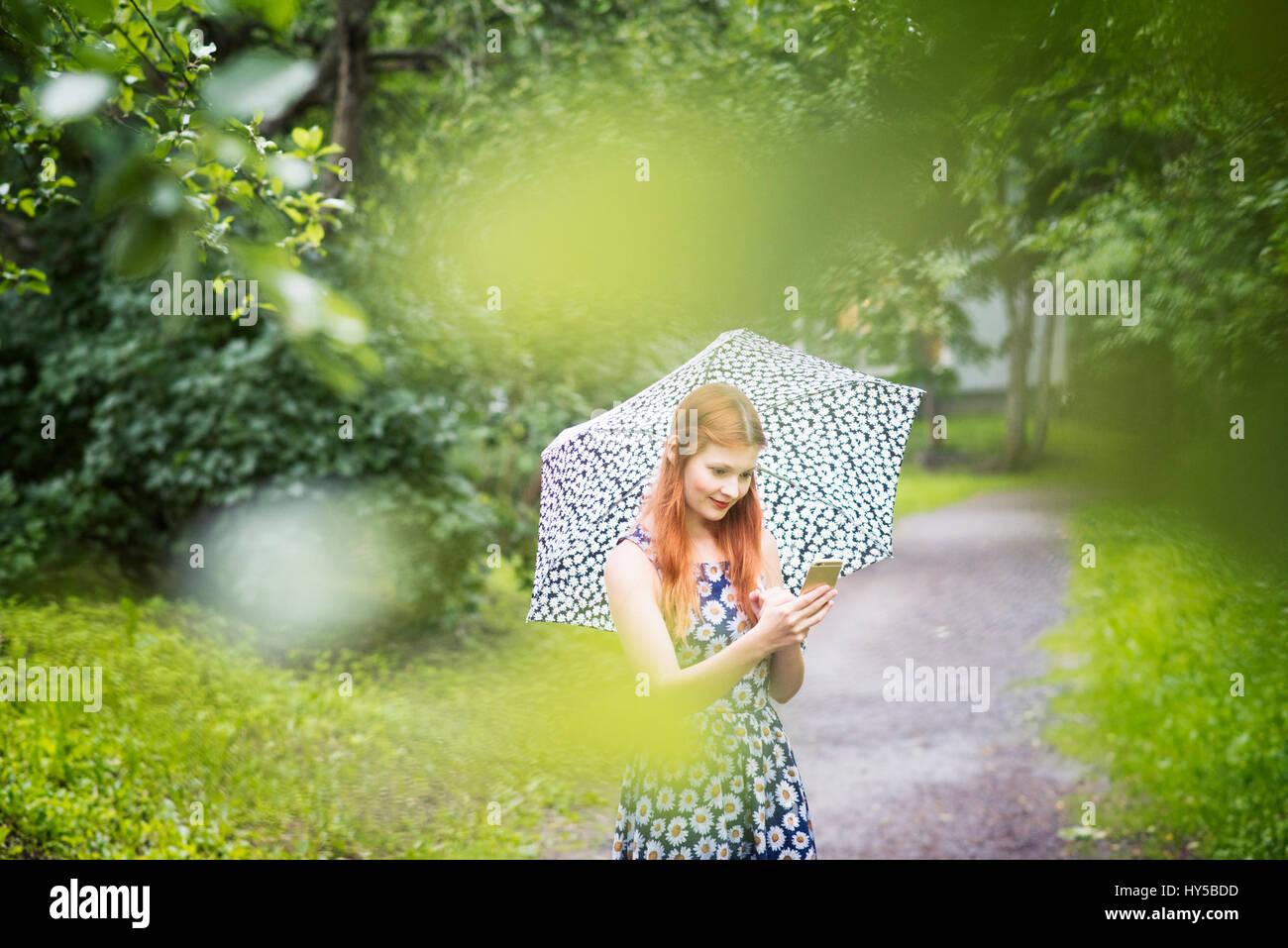 Finnland, Pirkanmaa, Tampere, Frau mit geblümten Kleid mit Regenschirm in Park Stockbild