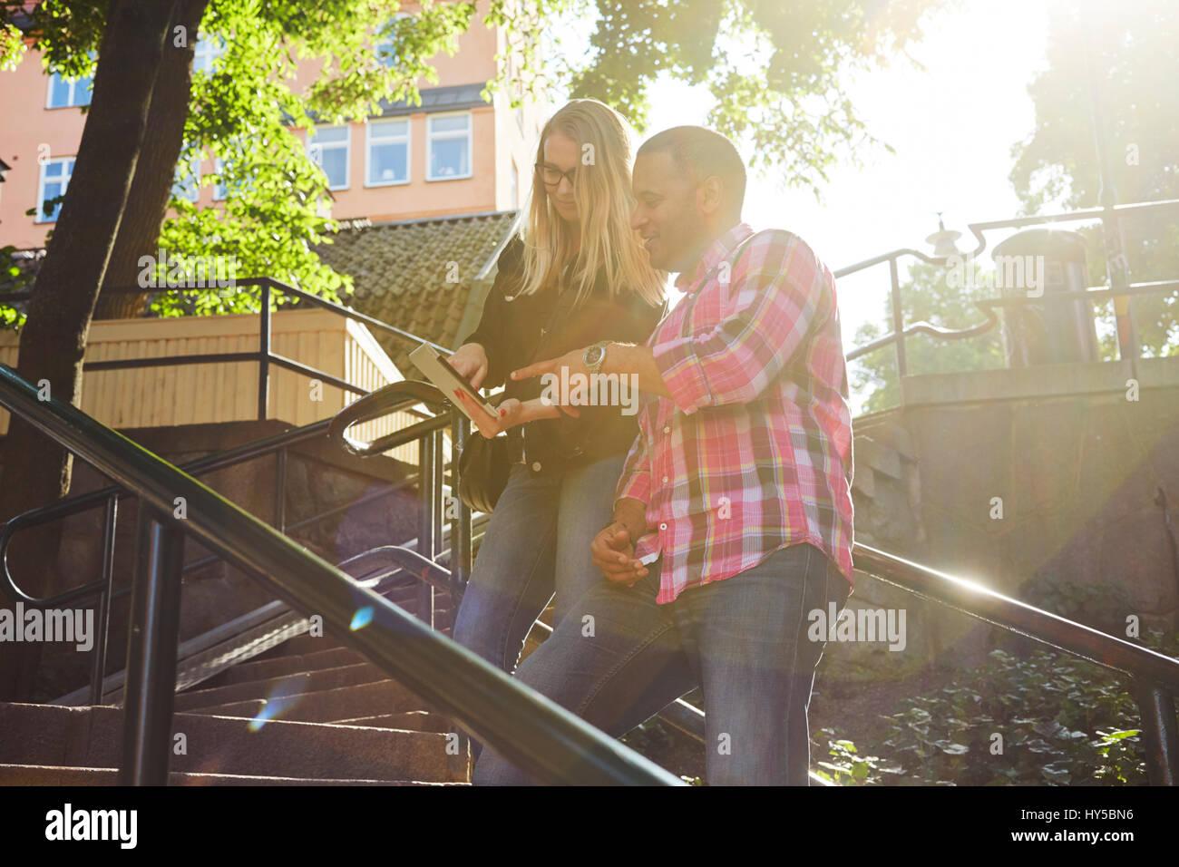 Schweden, Mann und Frau, nebeneinander auf digital Tablet im Sonnenlicht Stockbild
