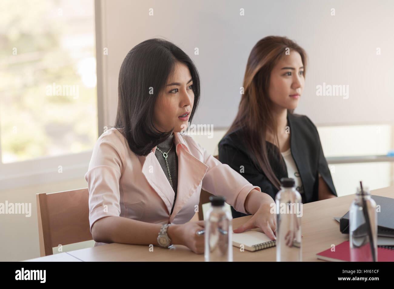 Zwei asiatische Unternehmerinnen achten Sie darauf, ihren Vorgesetzten während der Teilnahme an Business-Meeting Stockbild