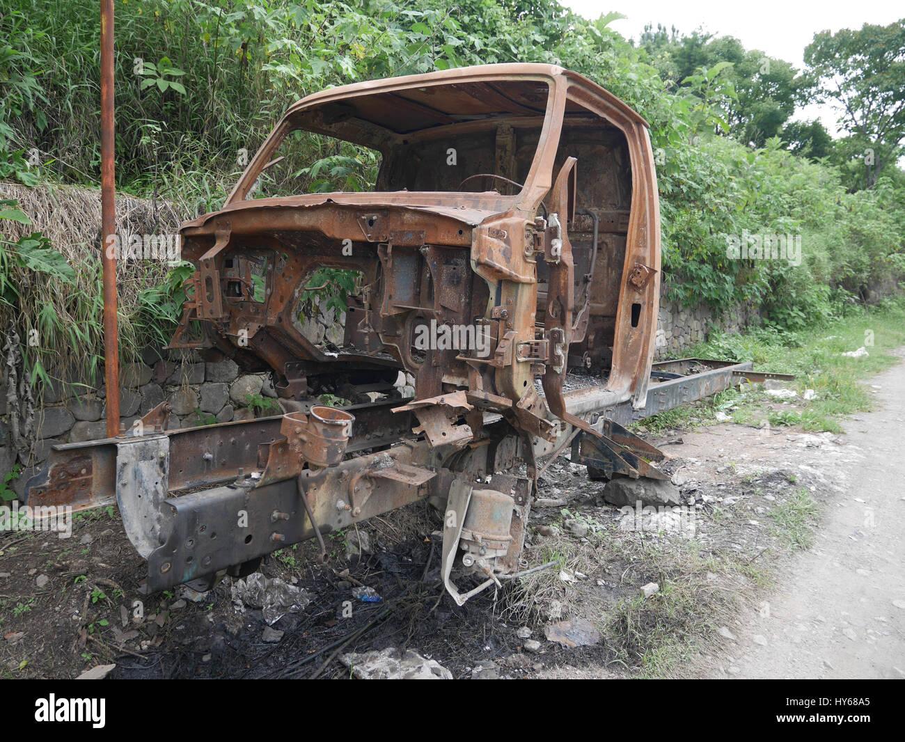 Alte verlassene rostige Rahmen eines LKW im Wald neben Straße ...