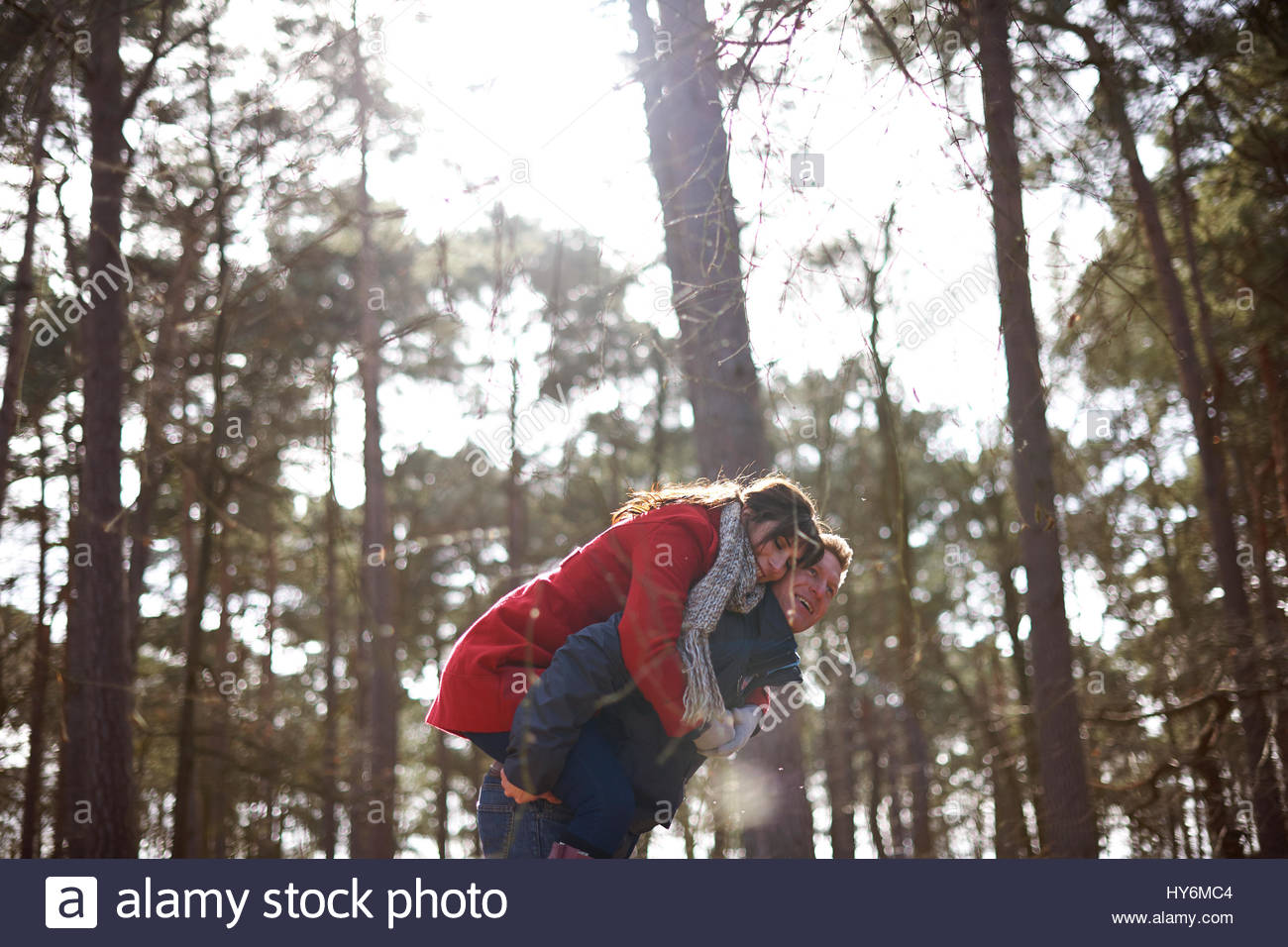 junger Mann geben junge Dame eine Huckepack Stockbild