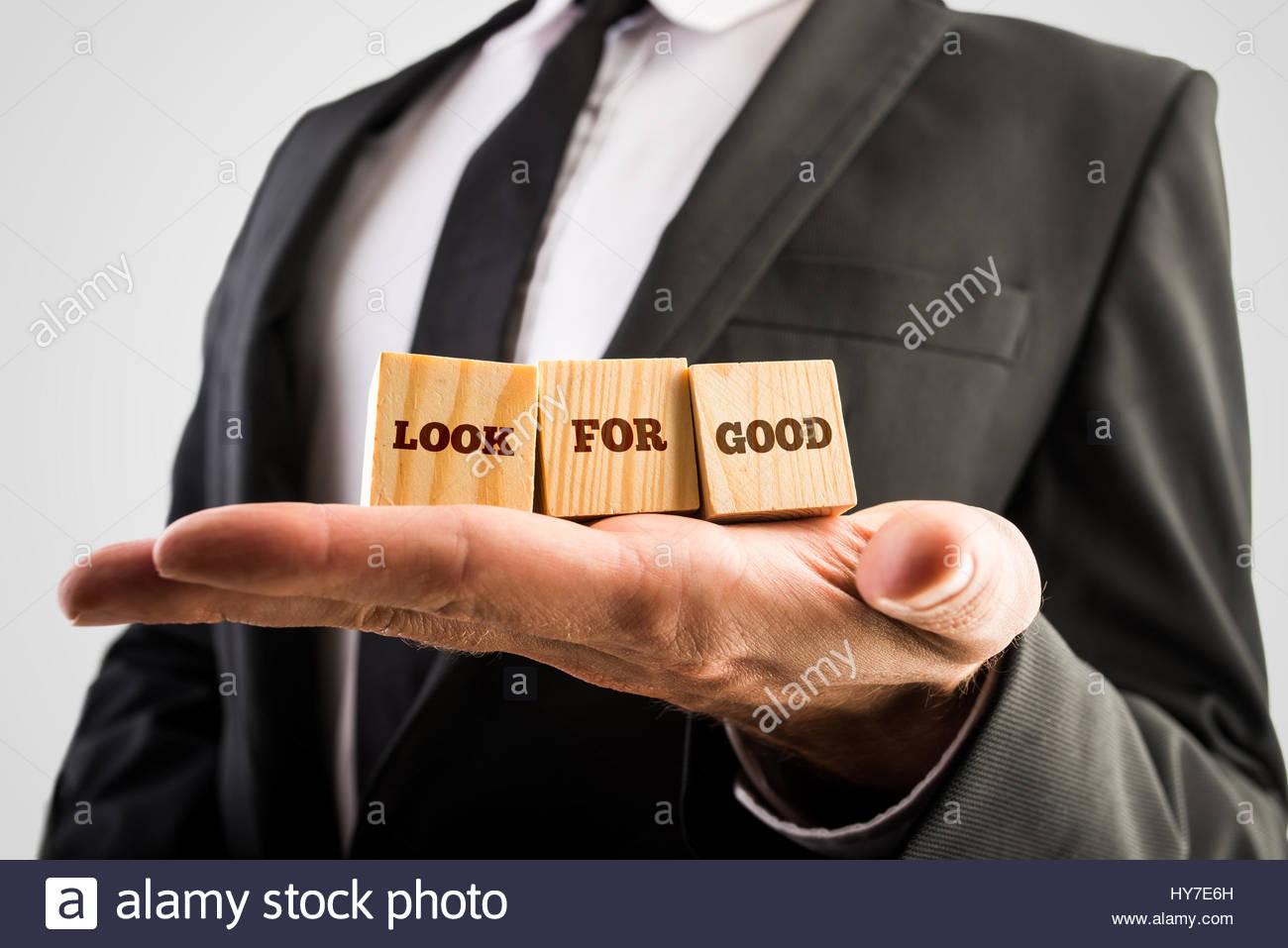 Nahaufnahme der männlichen Hand hält drei hölzerne Würfel mit einem Blick für guten Text. Stockbild