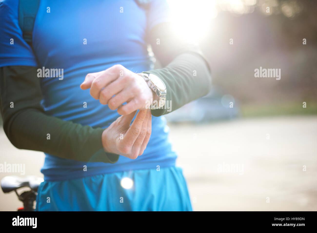 Ein Mann nimmt sich seine Uhr vor dem Training Stockbild