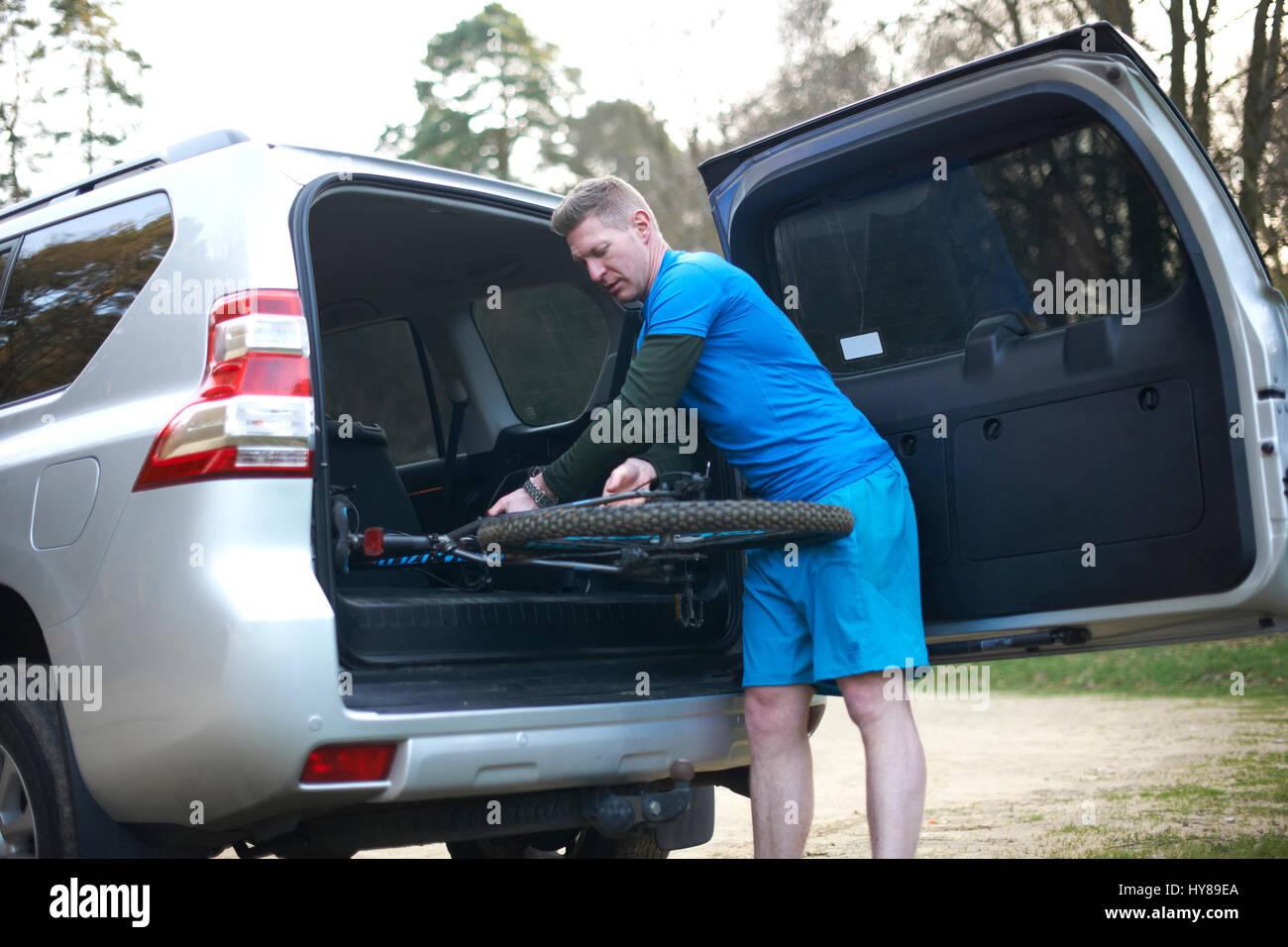 Ein Mann legt seinem Mountainbike wieder im Auto nach dem Training Stockbild