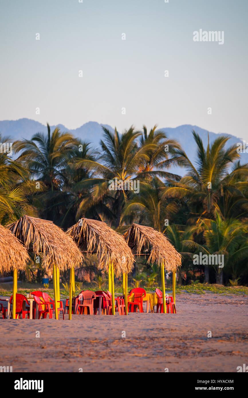 Rote Stühle, Palapas und Palmen säumen den Strand von San Blas, Nayarit, Mexiko. Stockbild