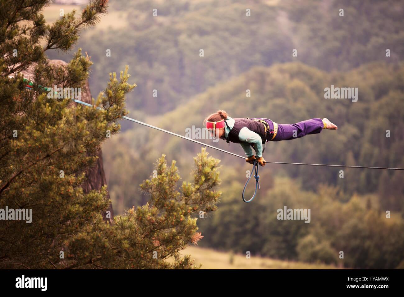 OSTROV, Tschechien: ein weiblicher Slackliner zeigt auf dem Hochseil. VON Verkleidung Kostüm Verleih-Draht Yoga Stockfoto