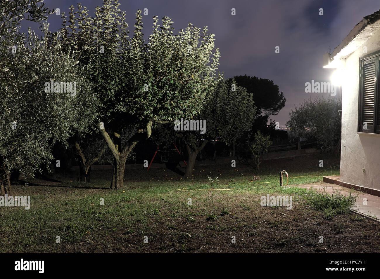 kleines haus auf dem land in der nacht mit außenbeleuchtung auf der