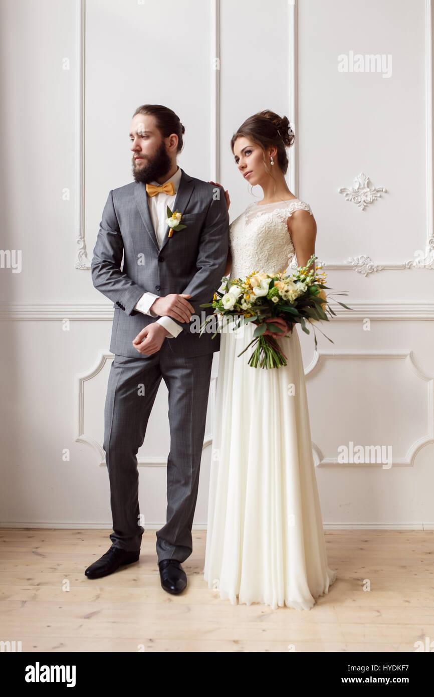 Porträt einer schönen Braut mit einem Blumenstrauß und Bräutigam mit ...