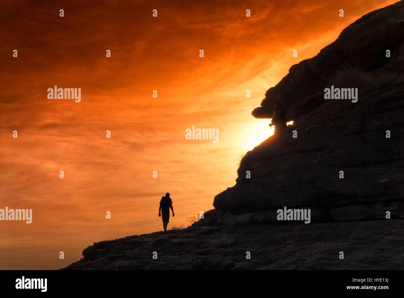 Silhouette der Wanderer in Richtung Sonnenuntergang mit orange glühenden Himmel klettern. Northern Territories, Stockfoto