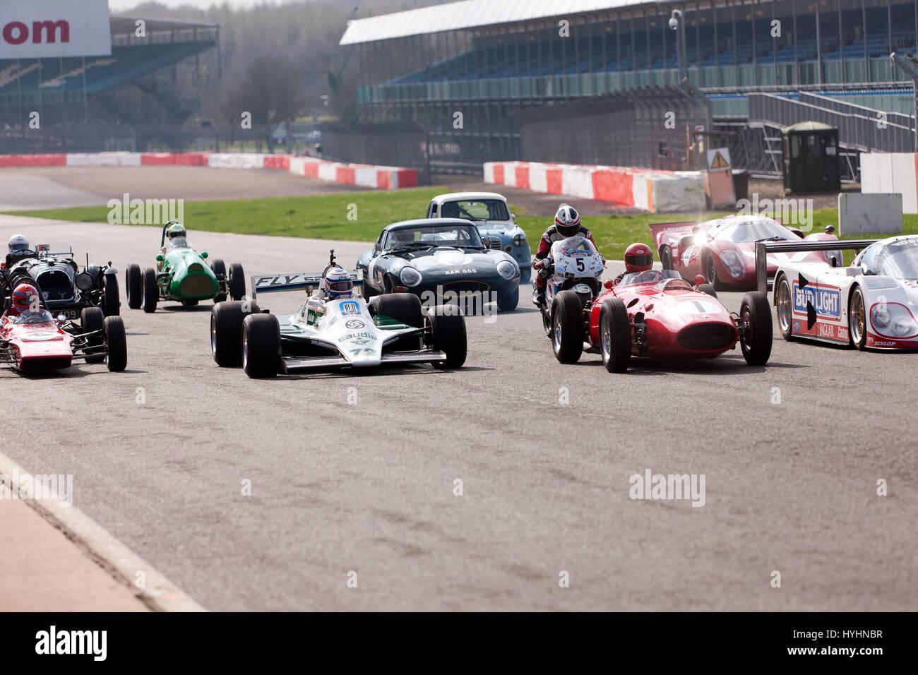 Eine Gruppe von klassischen Rennwagen aus verschiedenen Epochen und Gruppen, parade um dem Silverstone Circuit für Stockbild