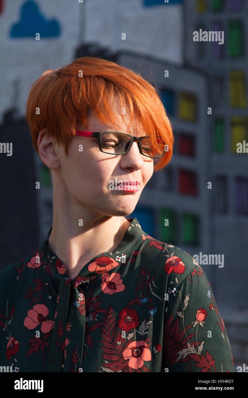 Das Mädchen Mit Kurzen Roten Haaren Mit Brille Lacht