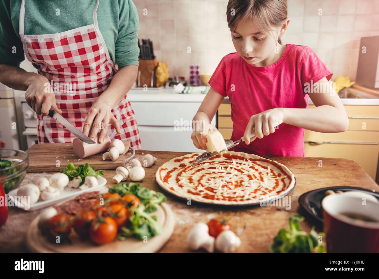 Mutter und Tochter, die Pizza in der Küche vorbereiten Stockbild