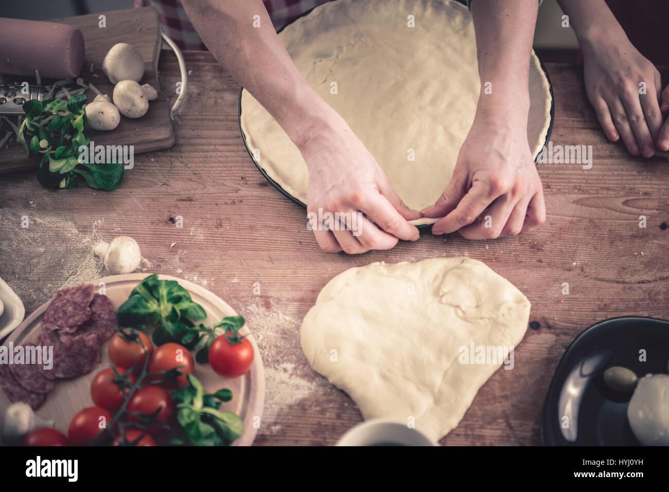Frau, die Pizza in der Küche vorbereiten Stockbild