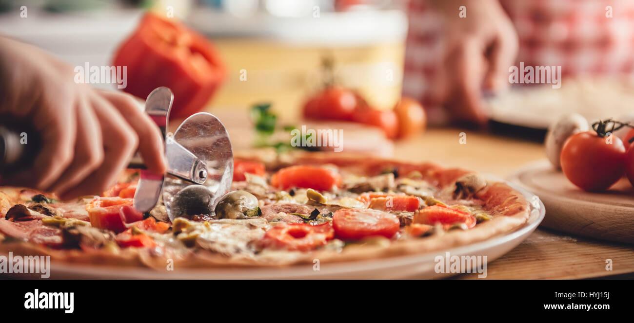 Frau schneiden frisch gebackene pizza Stockbild
