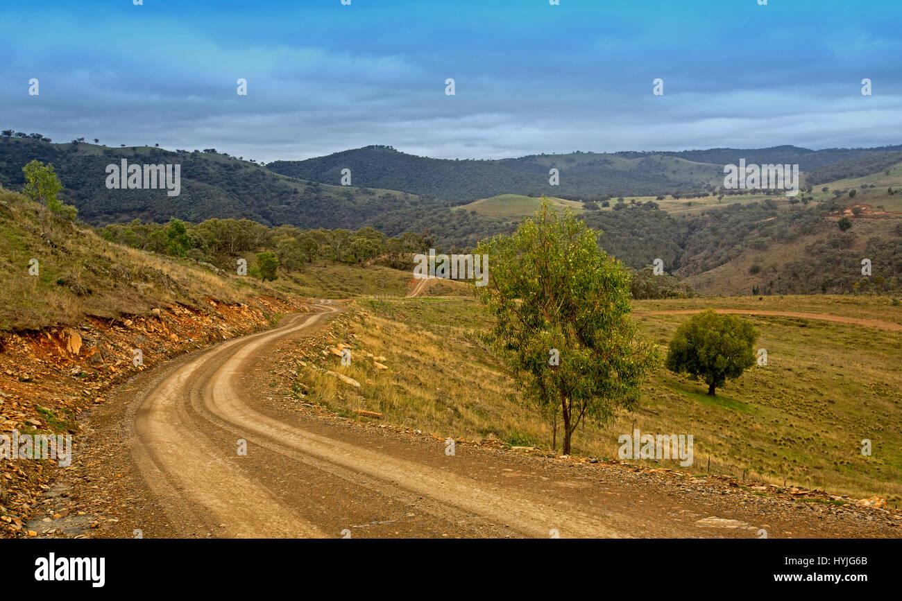 Schmale, unbefestigte Straße schlängelt sich durch weite Landschaft von bewaldeten Hügeln und Tälern Stockbild