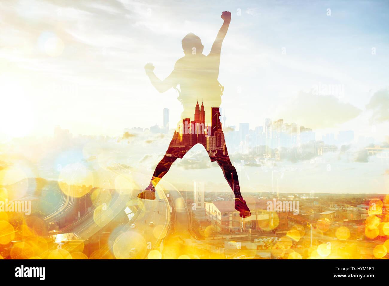 Mann springen auf dem Gipfel mit Panoramablick auf zeitgenössische Stadt Doppelbelichtung Effekt. Stockbild