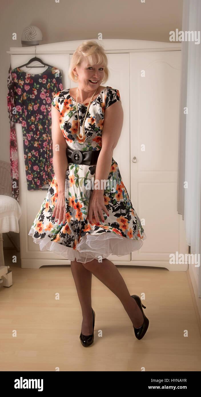 Eine reife Frau trägt ein florale Kleid mit einem weißen petticoat ...