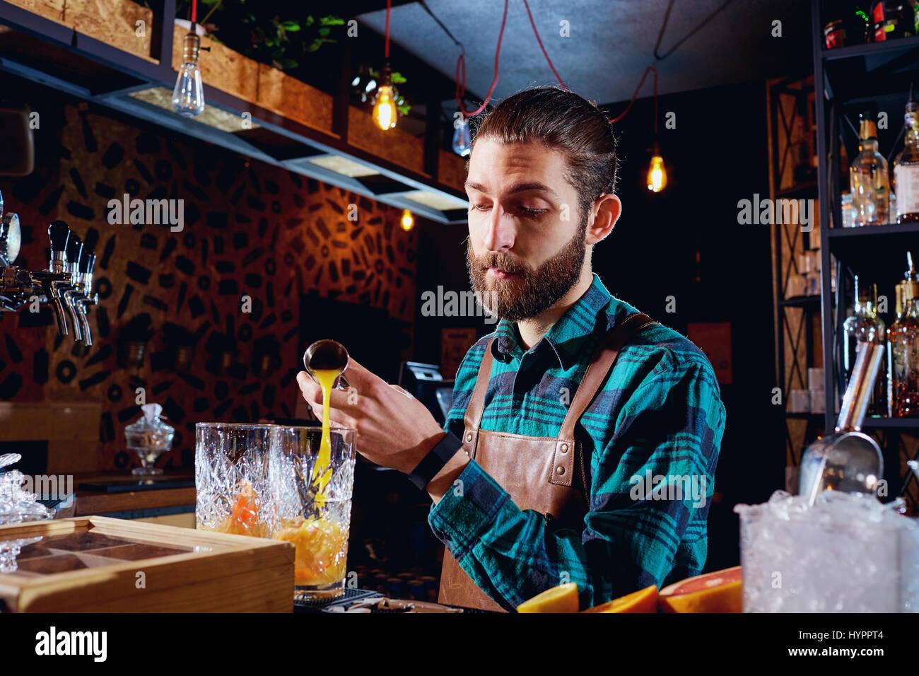 Der Barkeeper lacht machen einen Cocktail an der bar Stockbild