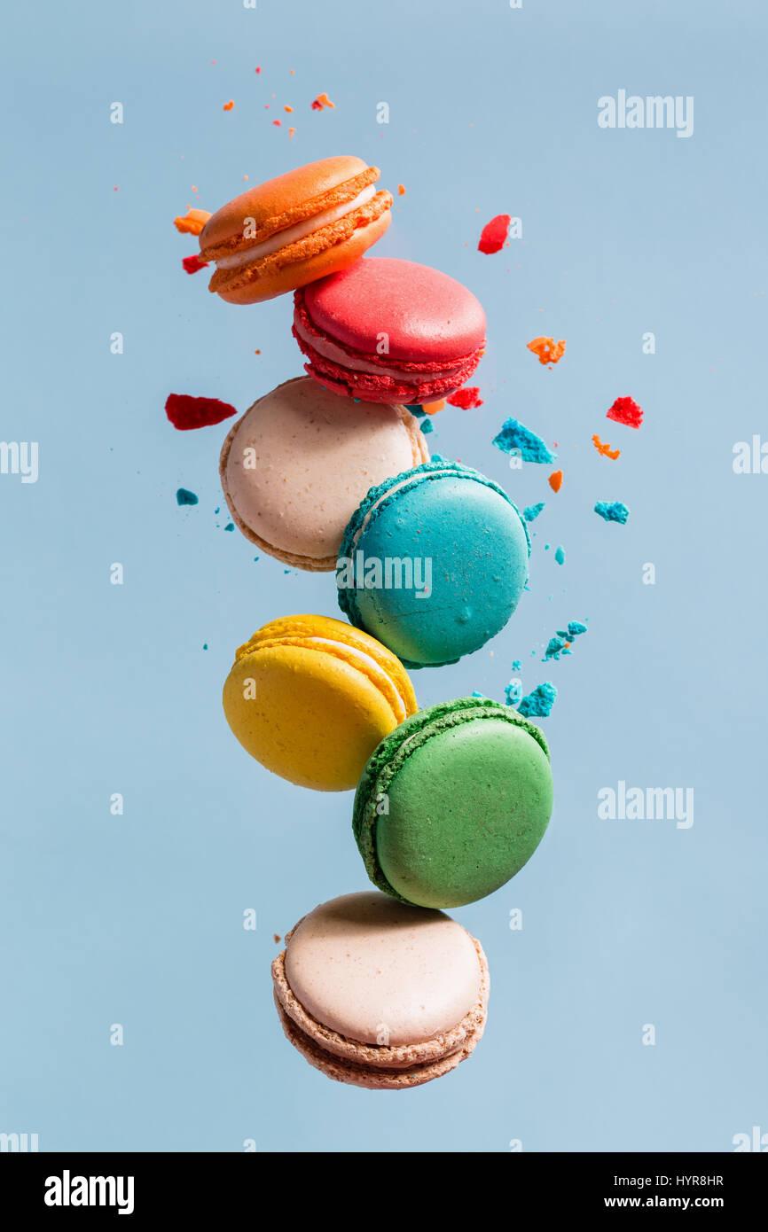 Verschiedene Arten von Makronen in Bewegung fallen auf Licht blauer Hintergrund. Süße und bunte französische Stockbild
