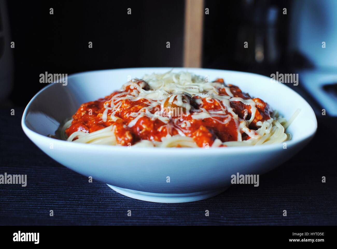 Leckere Spaghetti Bolognese mit Oliven und Mozzarella-Käse auf dunklem Hintergrund. Stockbild