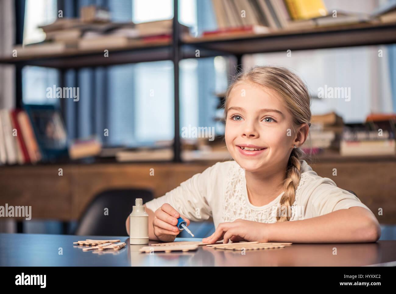Lächelnde Mädchen Handarbeit mit Eis-Sticks und Kleber Stockbild