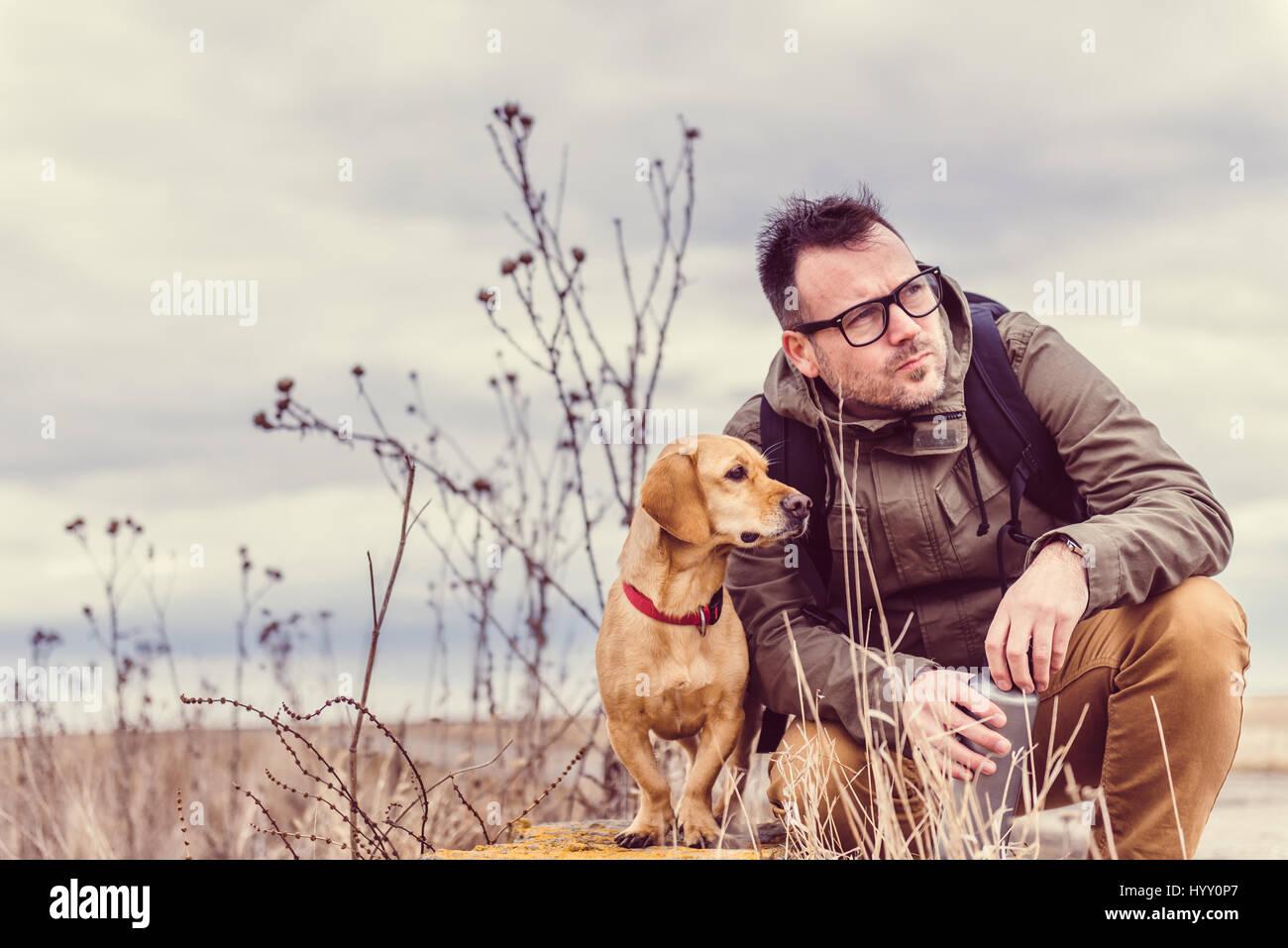 Wanderer und Hund ruht auf alte Mauer Stockbild