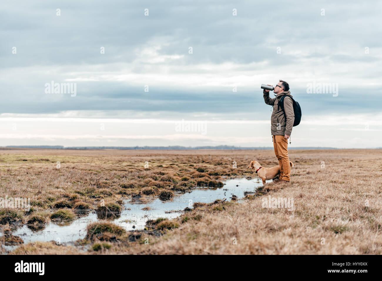 Wanderer und Hund stehend an einem bewölkten Tag am Teich in Grünland und Wasser zu trinken Stockbild