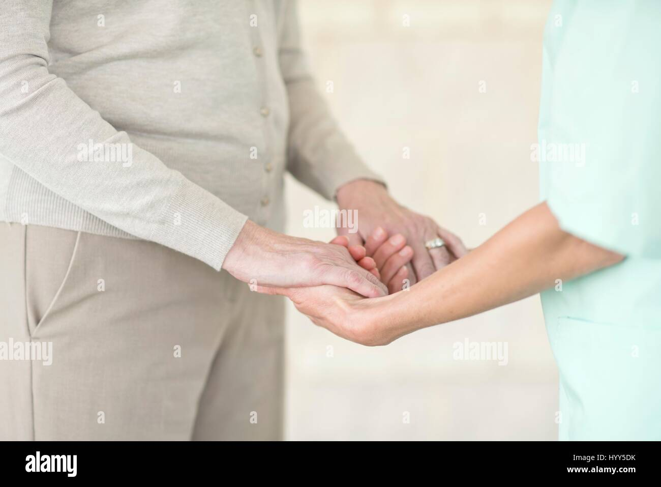 Pflegedienst senior Frau Händchenhalten. Stockbild