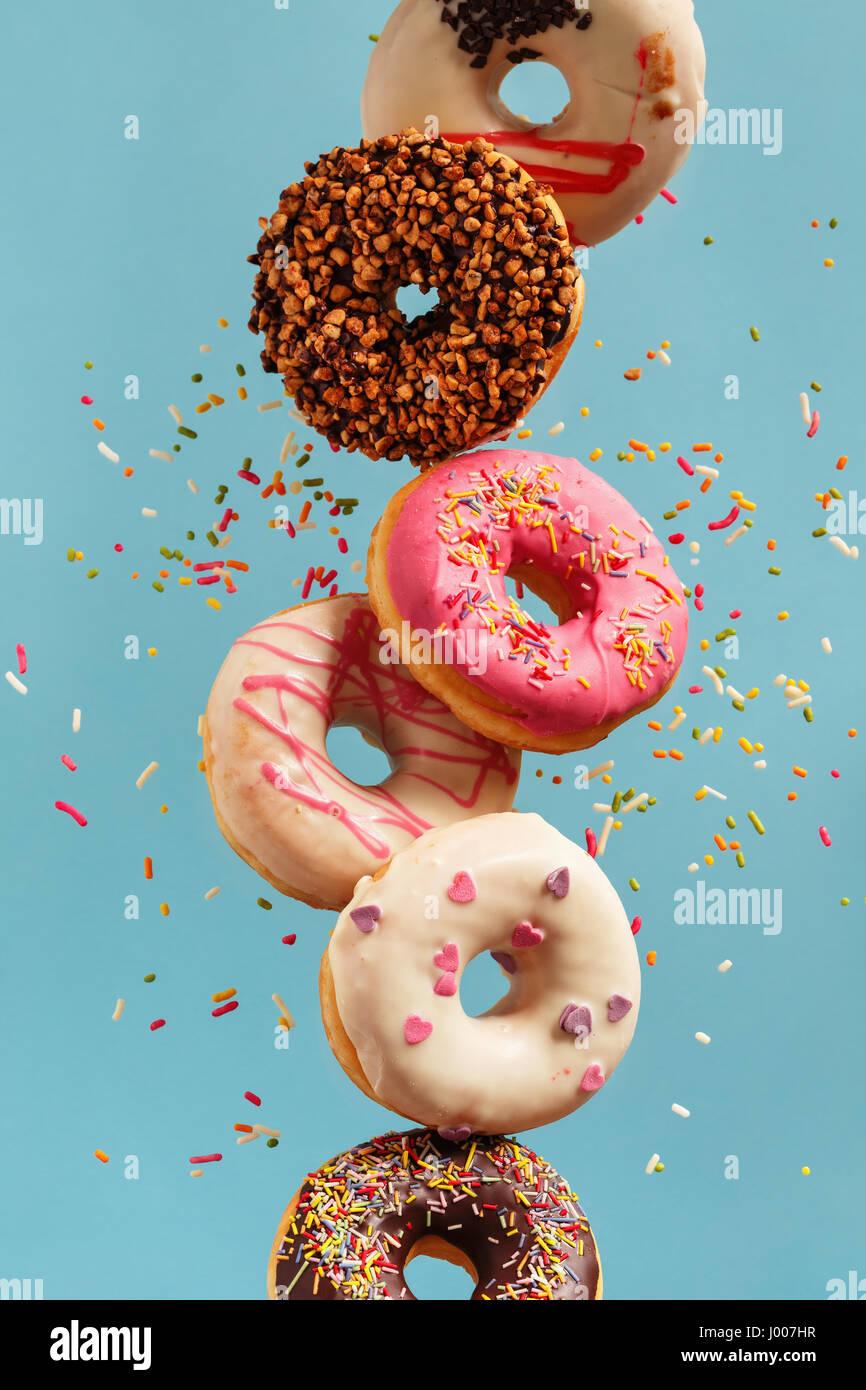 Verschiedenen dekoriert Krapfen in Bewegung fallen auf blauem Hintergrund. Süße und bunte Donuts fallen Stockbild