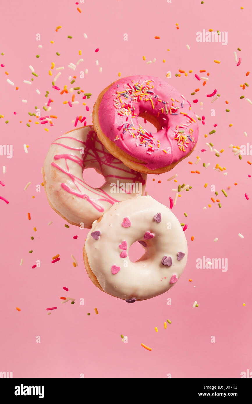 Verschiedenen dekoriert Krapfen in Bewegung fallen auf rosa Hintergrund. Süße und bunte Donuts fallen Stockbild