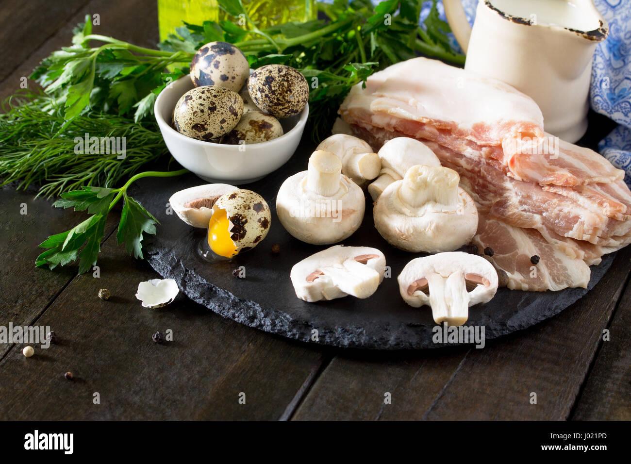 Kulinarisch - auf einer Schiefertafel Tafel Hintergrund Champignons, Schinken, Milch und Wachteleier. Frische Zutaten Stockbild