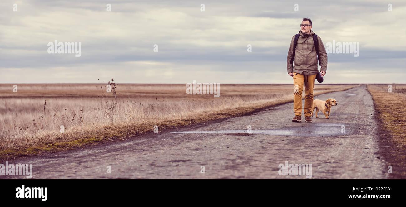 Wanderer und Hund zu Fuß hinunter eine Straße an einem bewölkten Tag Stockbild