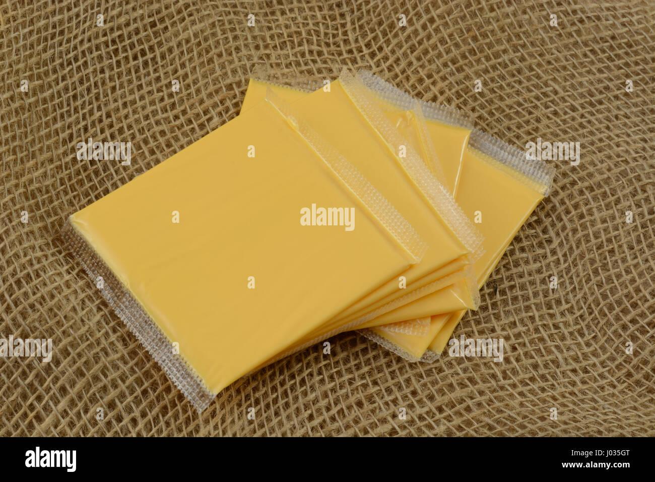 Stapel von amerikanischen Käsescheiben in Kunststoffverpackungen auf Sackleinen Stockbild