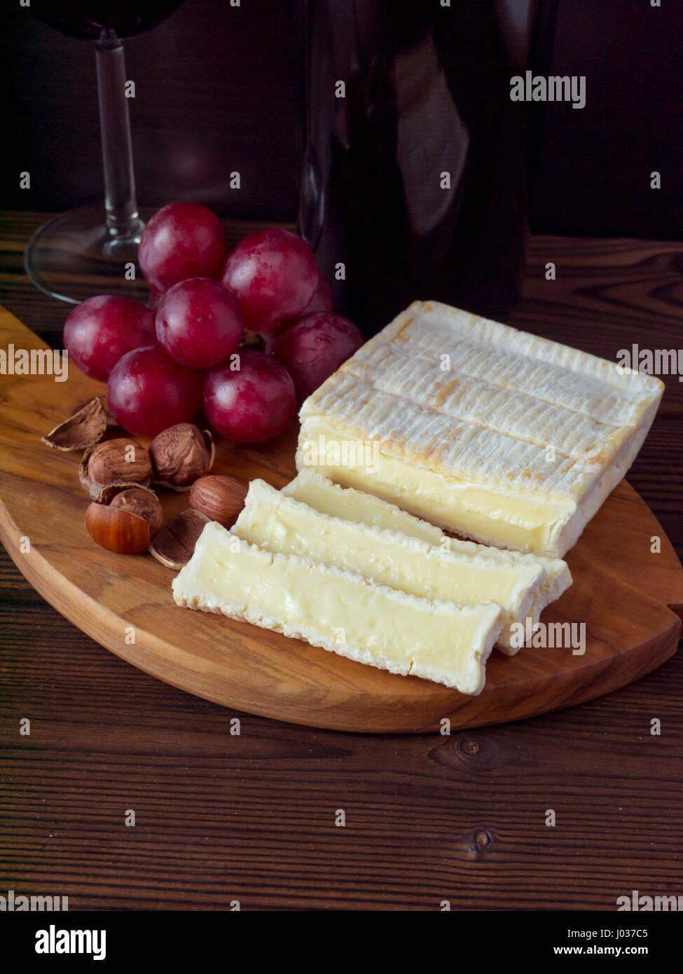 Ziegel geformt Käse mit weißen Schimmel, Haselnüsse, roten Trauben und Wein im Glas und Flasche Stockbild