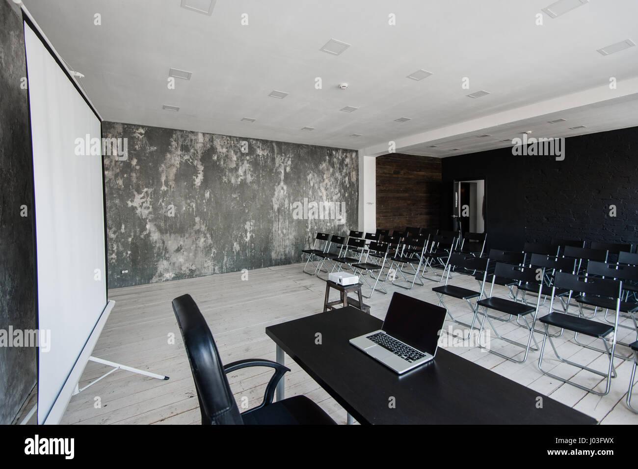 Raum für Vortrag mit vielen dunklen Stühlen. Wände sind weiß, Loft ...