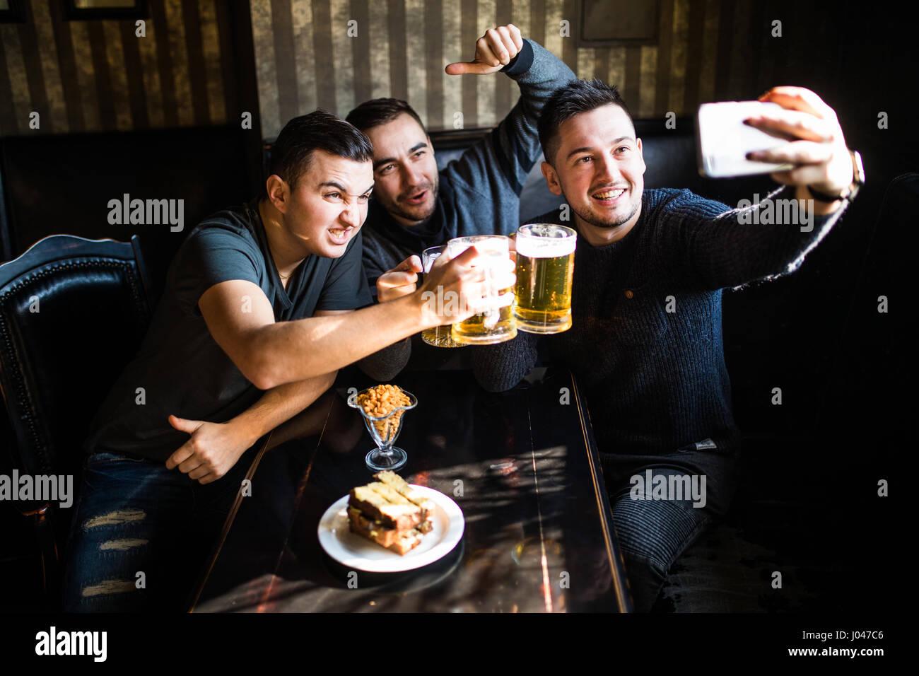 Leute, Freizeit, Freundschaft, Technologie und Party-Konzept - glücklich männlichen Freunden nehmen Selfie Stockbild