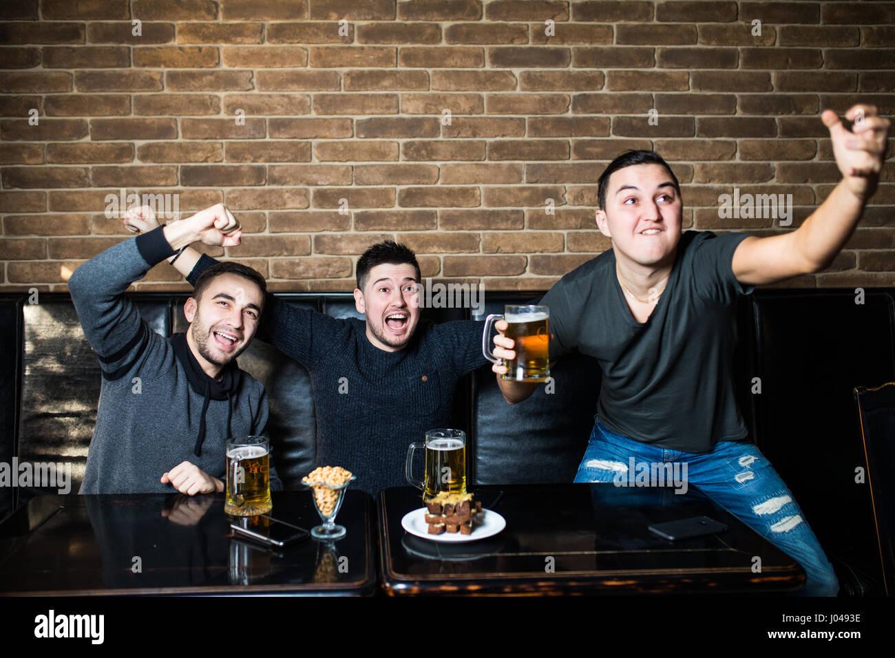 Junge Männer trinken Bier, Essen, Snacks und Jubel für Fußball. Stockbild
