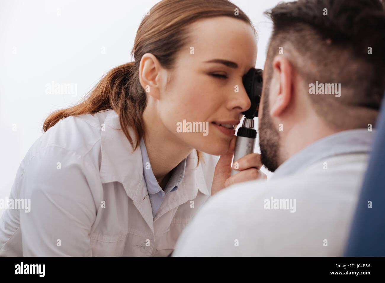 Schöne professionelle Optiker mit einem modernen Diagnosegerät Stockbild
