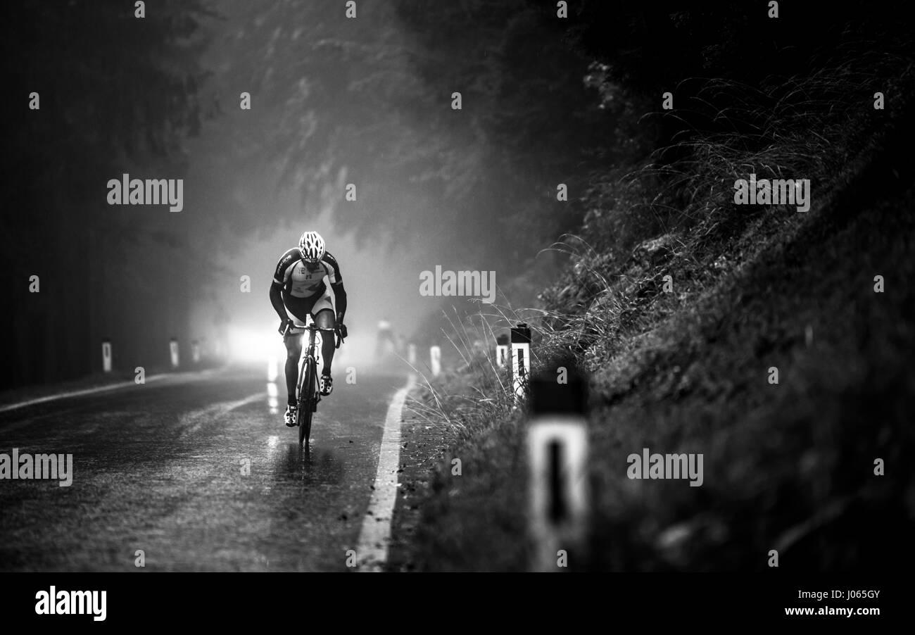 Ein professioneller Fahrradrennen hinauf Geisberg bei nebligen und regnerischen Wetter beim Road Racing Bike Race Stockbild