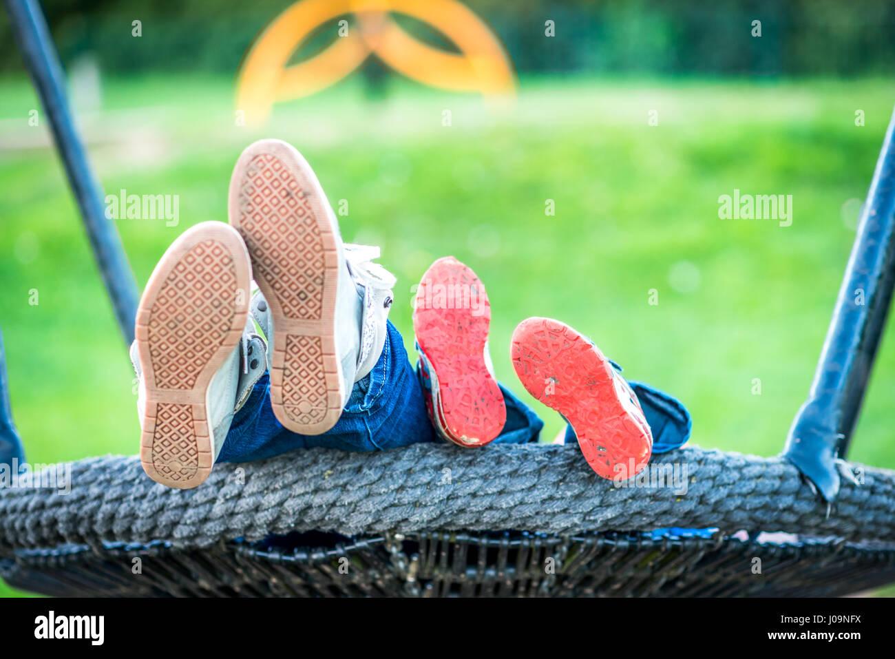Tag-Ansicht Mutter und Kind Füße auf Schaukeln. Stockfoto